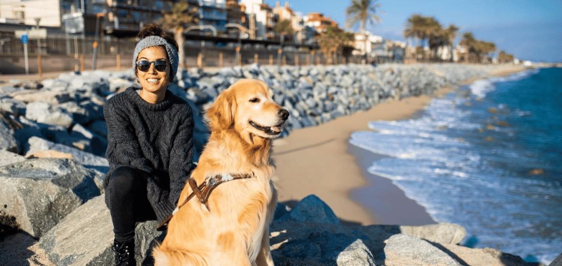 María junto a su perro guía Tavish frente al mar