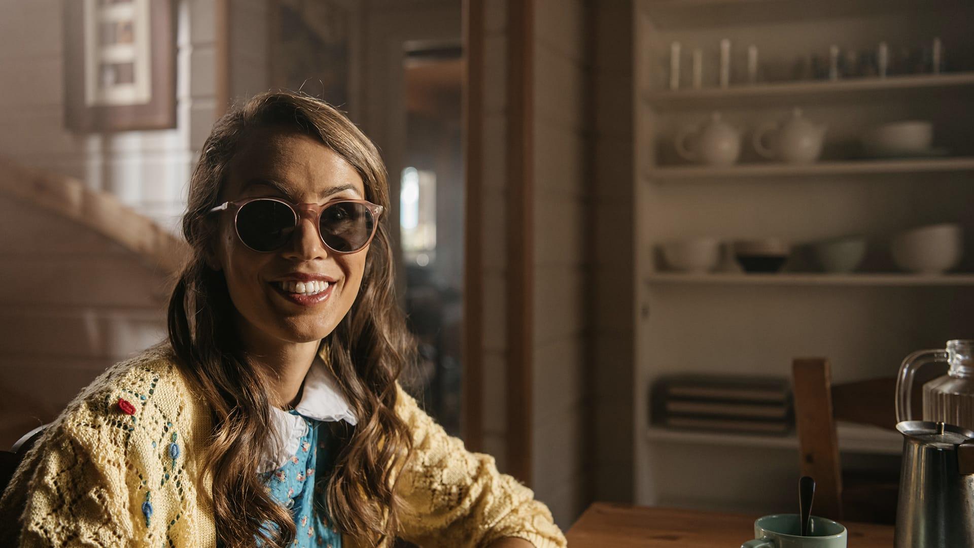 María Petit sonríe en primer plano sentada en la mesa de la cocina. en el vídeo de la semana de la discapacidad
