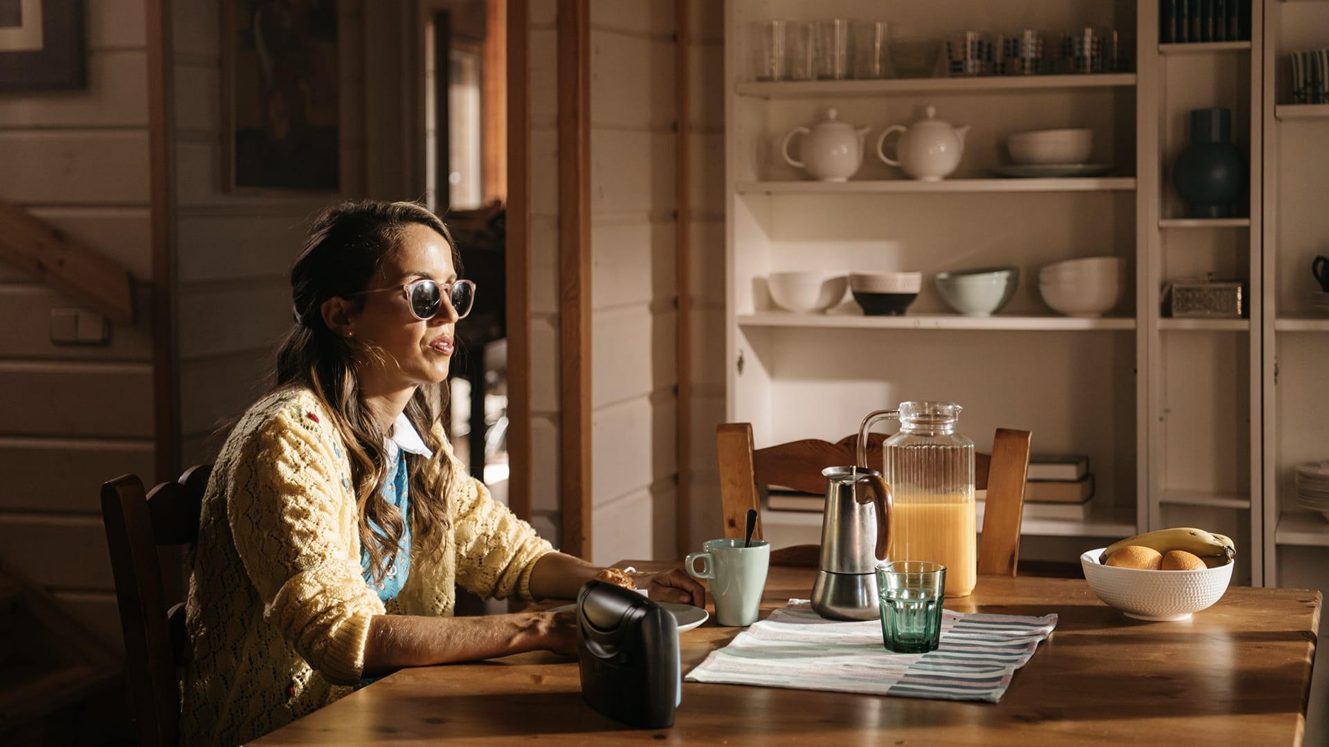 María Petit sentada en la mesa del desayuno junto a la radio.