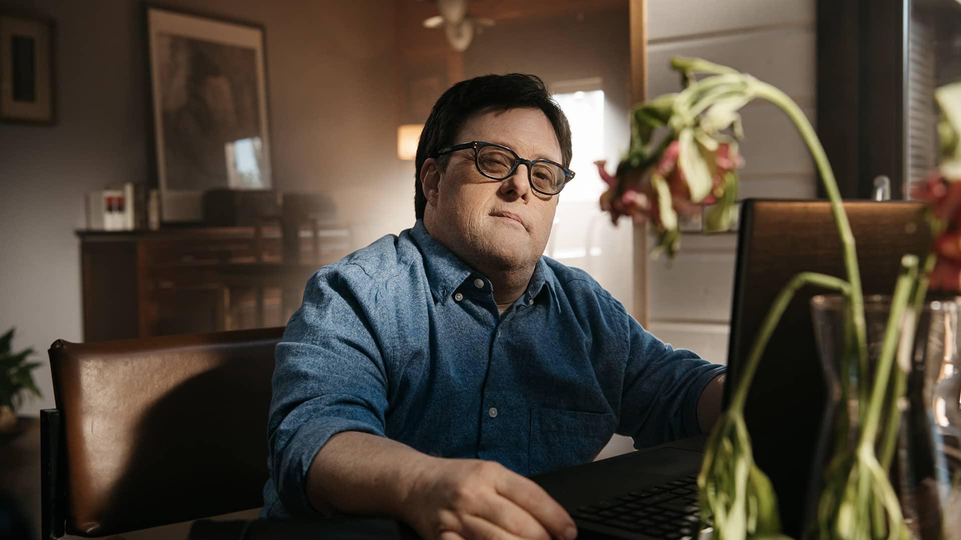 Pablo Pineda, frente al ordenador, detrás de una flor marchita.