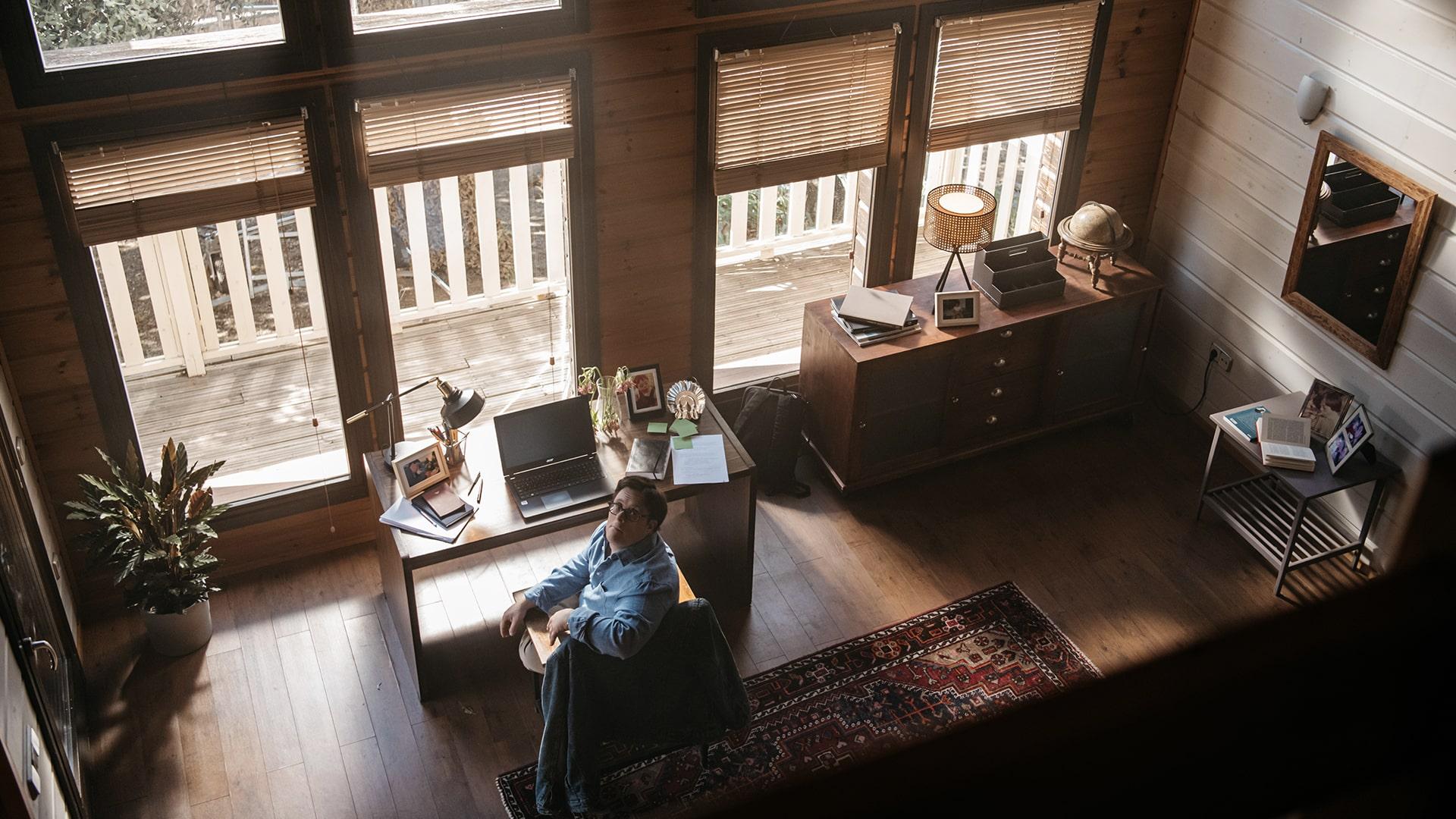 Pablo Pineda, sentado en el escritorio delante de un ordenador, frente a un gran ventanal, mira hacia arriba, donde está situado el objetivo de la cámara.