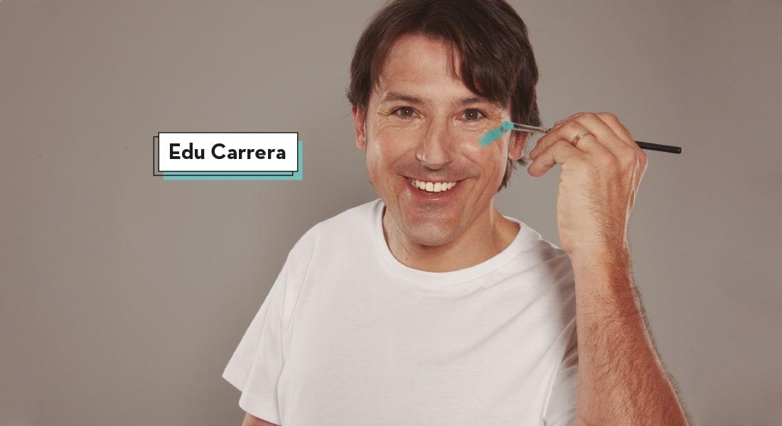 Edu Carrera con pincel cogido con su mano izquierda se dibuja una linea de color azul sobre su mejilla izquierda en defensa de la igualdad de oportunidades y el empleo