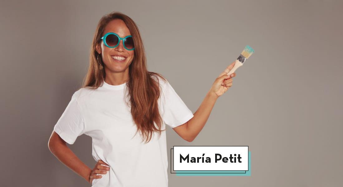 Maria Petit, embajadora de la Fundación Adecco, con su mano derecha apoyada en su cintura, sonríe a cámara mientras sujeta con su mano izquierda un pincel manchado de color azul que apunta ligeramente hacia la derecha